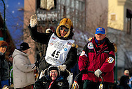 04 March 2006: Anchorage, Alaska - Ryan Redington, grandson of Iditarod co-founder, Joe Redington, heads out for his third Iditarod race, waving to the fans during the Ceremonial Start in downtown Anchorage.