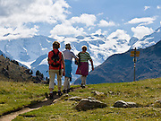 "Hikers walk at Alp Languard, a chairlift station above Pontresina, with good views of the Bernina massif, in Upper Engadine, Grison Alps, Switzerland, Europe. The Swiss valley of Engadine translates as the ""garden of the En (or Inn) River"" (Engadin in German, Engiadina in Romansh, Engadina in Italian)."