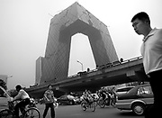 Traffic passes the construction site of the CCTV tower in eastern Beijing.