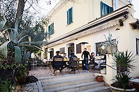 """ROME, ITALY - 7 January 2014: Customer sit for lunch or for a coffee on the terrace of Bar Necci, an airy bar and restaurant that was made famous by the Italian director Pier Paolo Pasolini who shot parts of his 1961 film """"Accattone"""" in the Pigneto neighborhood of Rome, Italy, on February 7th 2014."""