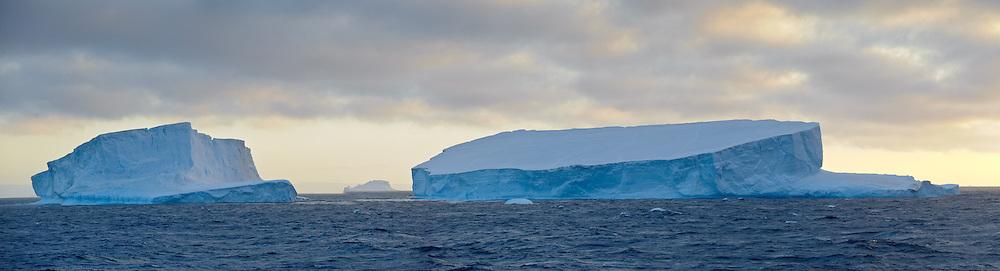 Sunset over two massive icebergs in Antarctica
