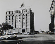 Photograph showing view of the Texas School Book Depository Building from Elm Street, Dallas, Texas...Photograph: Warren Commission/ Dennis Brack Archives