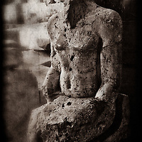 A black and white creative photograph of a ruined statue of an unknown person. Built circa 1400 BC. Karnak Temple, Egypt.