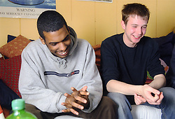 Two teenage boys sitting together laughing,