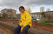 Young black boy sitting on brick wall with housing estates in the background, London, UK, 2000's