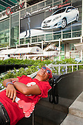 """Apr 4, 2010 - BANGKOK, THAILAND: A Red Shirt protestor sleeps on the stairs in front of Central World Plaza, one of the malls in Bangkok that closed the Red Shirts moved into central Bangkok. Thousands of members of the United Front of Democracy Against Dictatorship (UDD), also known as the """"Red Shirts"""" and their supporters moved their anti government protests into central Bangkok Apr. 4 when they occupied Ratchaprasong intersection, the site of Bangkok's fanciest shopping malls and several 5 star hotels. The Red Shirts are demanding the resignation of current Thai Prime Minister Abhisit Vejjajiva and his government. The protest is a continuation of protests the Red Shirts have been holding across Thailand. They support former Prime Minister Thaksin Shinawatra, who was deposed in a coup in 2006 and went into exile rather than go to prison after being convicted on corruption charges. Thaksin is still enormously popular in rural Thailand. This move, away from their traditional protest site in the old part of Bangkok, has gridlocked the center of the city and closed hundreds of stores and restaurants and several religious shrines. There has not been any violence, but the government had demanded that the Red Shirts return to the old part of the city.   PHOTO BY JACK KURTZ"""