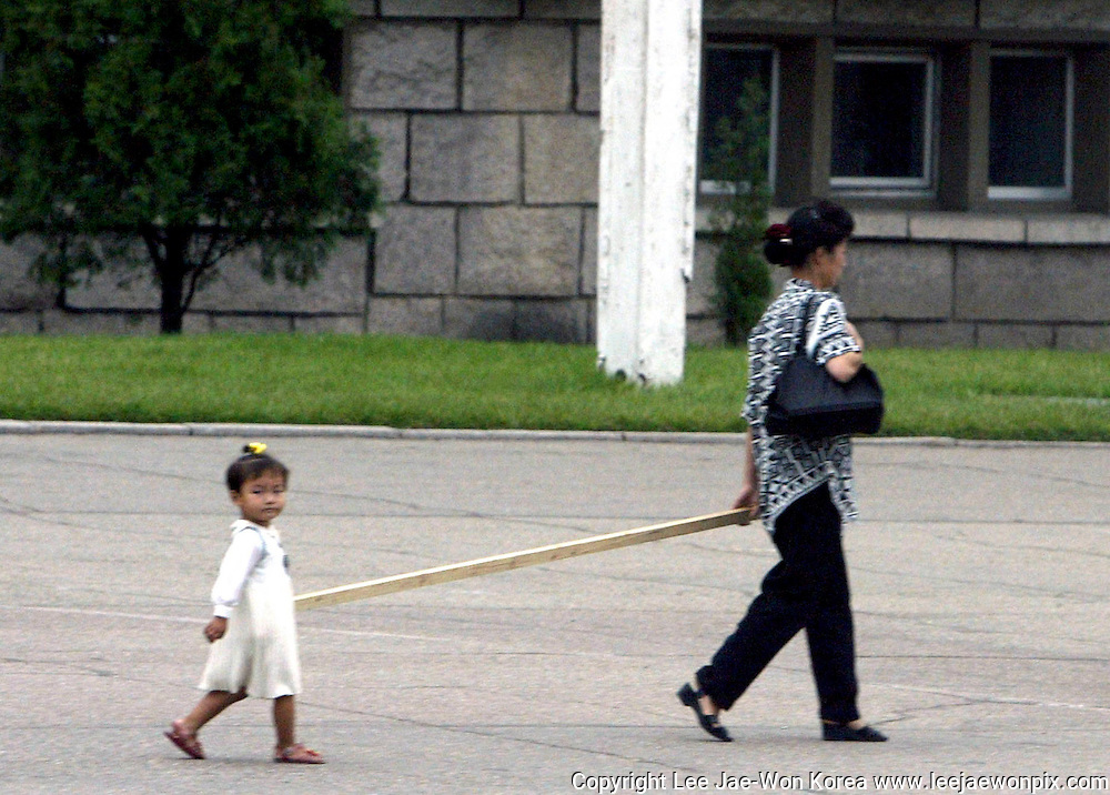A North Korean child and her mother carry a pole in Pyongyang August 17, 2003. /Lee Jae-Won