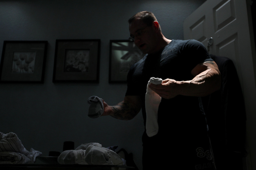 Convicted steroid dealer David Jacobs folds laundry at his home in Plano Wednesday April 30, 2008.  He was found dead in his home one year later--a supposed suicide.