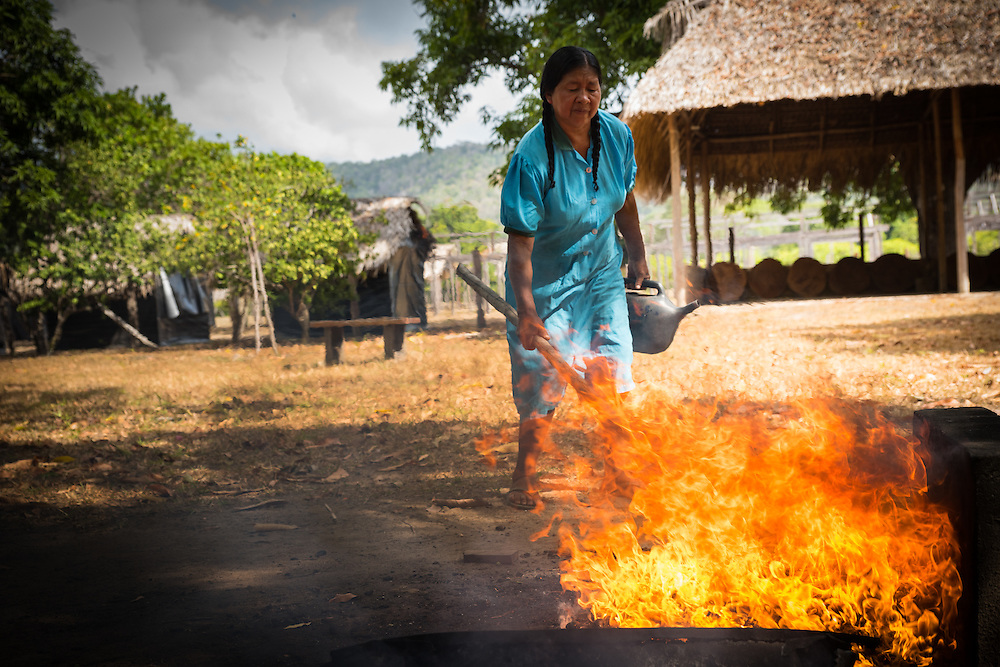 Woman roasts cashewnuts on a farm, Rupununi, Guyana.