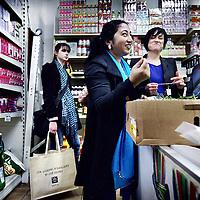 Nederland, Amsterdam , 21 mei 2013..De lancering van de Javatas..De liefde voor eten, bijzondere keukengeheimen en mooie verhalen, zijn verzameld in de Javatas. De Javatas verbindt producten van de winkeliers uit de Amsterdamse Javastraat met de persoonlijke verhalen, recepten en portretten van zes buurtbewoners uit de Indische buurt in Amsterdam-Oost..Na de presentatie neemt de Pakistaanse Ferdousi de pers en geinteresseerden mee langs de winkels in de Javastraat waar zij haar voedselproducten koop zoals hier in een Pakistaanse kruidenier en geeft uitleg omtrent de ingredienten in 1 van haar recepten. .Op de achtergrond initiatiefneemster Maureen de Jong. (met blauw shirt).De Javatas is een initiatief van Maureen de Jong en Heike Hamelink en wordt mogelijk gemaakt door 'Samen Indische buurt'..Foto:Jean-Pierre Jans