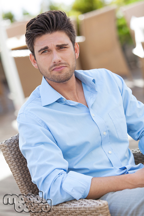 Young man sitting on chair at outdoors cafe