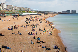 © Licensed to London News Pictures. 04/05/2019. Brighton, UK. A handful of visitors can be seen enjoying the sunshine on the beach in Brighton and Hove as colder weather is hitting the seaside resort on the 2019 May Bank holiday Saturday. Photo credit: Hugo Michiels/LNP