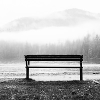 A lone park bench by the waters edge with fog in the trees and mountains, in the background.