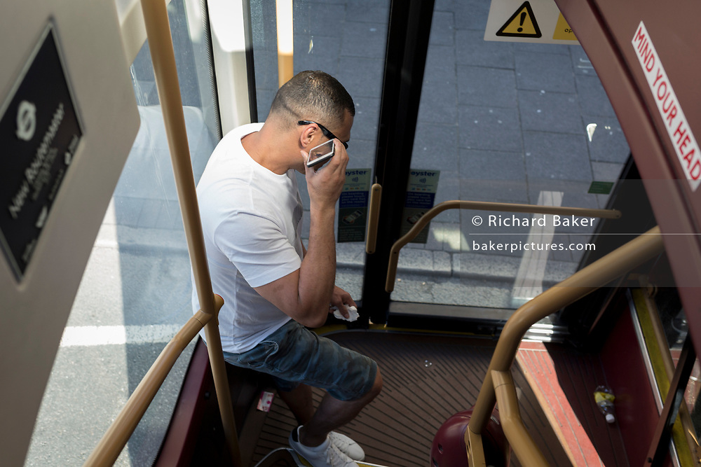 While listening to the speaker of his phone, a bus passenger stands at the rear door of a double-decker ('Boris') Routemaster bus in Southwark, on 15th June 2019, in London, England.