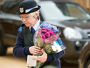 © Licensed to London News Pictures. 23/04/2014. New Malden, UK . A PCSO delivers flowers to the scene. The scene in New Malden where a woman has been arrested after the discovery of three bodies of children in a house overnight. Photo credit : Stephen Simpson/LNP