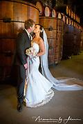 Bride and groom kissing in winery beside barrels.