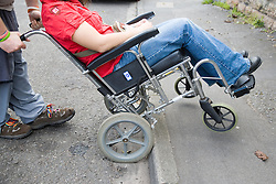 Man pushing young woman with cerebral palsy in a wheelchair up a curb,