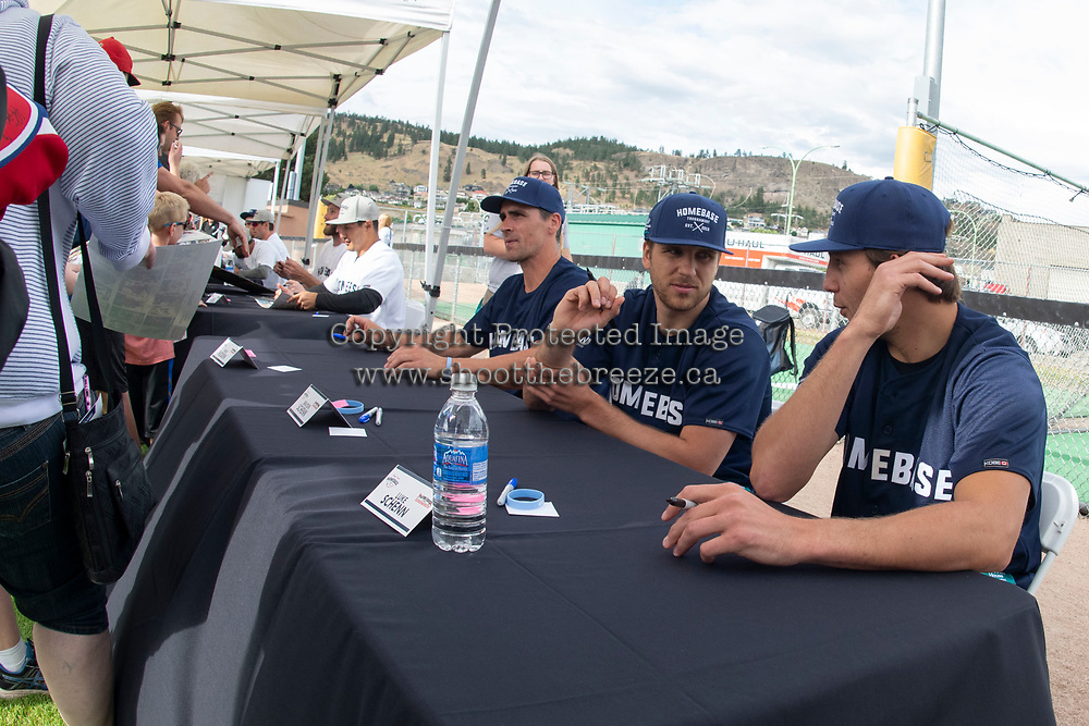 KELOWNA, CANADA - JUNE 28: Retired NHL player Wade Redden, 2019 Stanley Cup Champion St. Louis Blues player Brayden Schenn and Vancouver Canucks player Luke Schenn sit at a table during an autograph signing prior to the opening charity game of the Home Base Slo-Pitch Tournament fundraiser for the Kelowna General Hospital Foundation JoeAnna's House on June 28, 2019 at Elk's Stadium in Kelowna, British Columbia, Canada.  (Photo by Marissa Baecker/Shoot the Breeze)