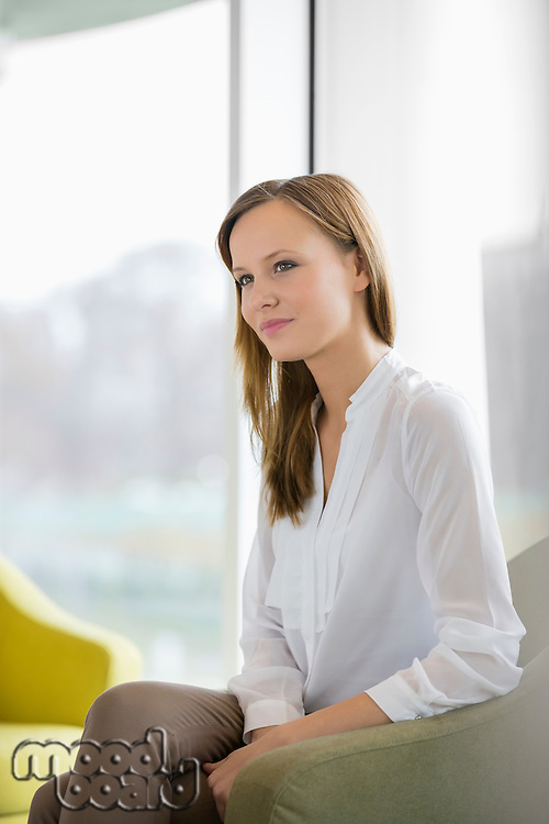 Thoughtful young businesswoman in office lobby