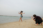 Israel, Tel Aviv, Teen Aged girl of 14 dancing on the beach while a teen boy takes her picture