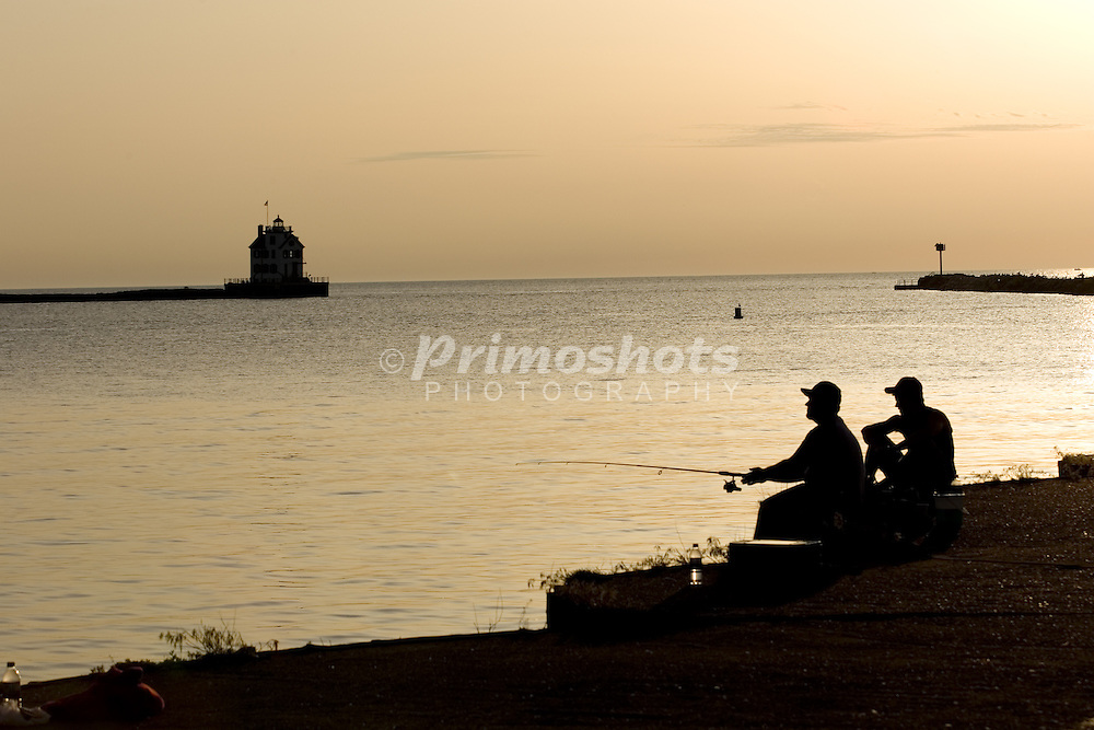 Two men sit on a pier fishing at sunset.