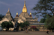 Local Burmese cycle past Ananda Temple of Bagan,one of the most sacred of the hundreds that litter the plain on the banks of the Irrawaddy River.