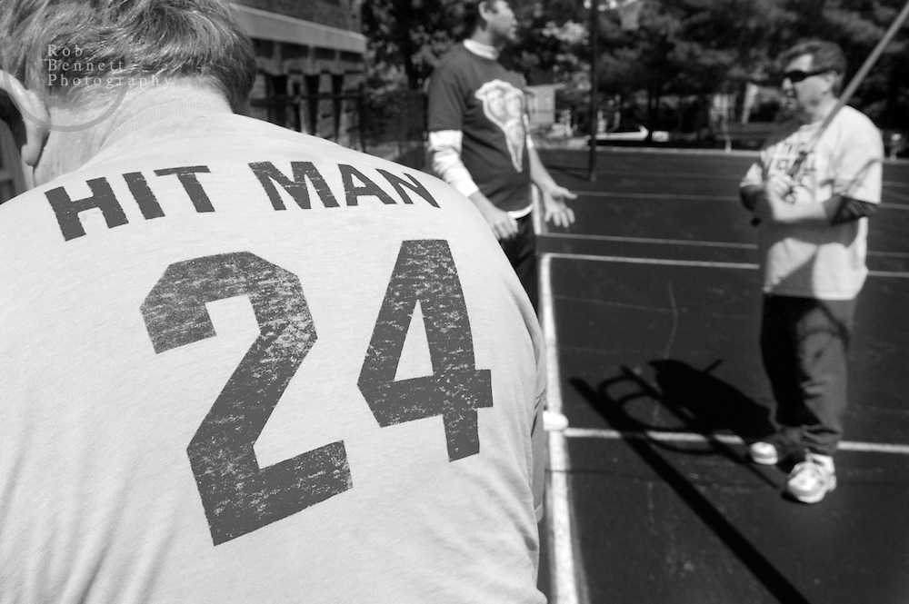"""Howard """"Hit Man"""" Weishaus (back to camera), 68 and a teacher from New City, gathers his equipment in preparation for another day of stickball while Andy Ettinger (C) and Jack """"Late Lightning"""" Dammann (R) chat in the background..---.The Ethical Stickball League has been operating since 1970, meeting every Sunday in the parking lot behind Hastings High School from 10:30AM to 1PM.  The players are men now mostly in their 70s - carrying nicknames like """"The Wise One"""", """"Hit Man"""" and """"Plays Hurt"""" - who have an affiliation with the school, either as former teachers, students or neighbors. As their slogan suggests, all it takes for a few hours of """"Aestas Aeterna"""" (Eternal Summer) is an outside temperature above 45 degrees and 8 willing souls...CREDIT: Rob Bennett for The NY Times"""