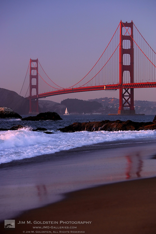 The Golden Gate Bridge at sunset reflected in the sands of Baker Beach, San Francisco.