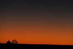 The Lower Fox Creek Schoolhouse and a lone cottonwood tree are silhouetted against a clear sky during a fall sunrise at the Tallgrass Prairie National Preserve. The 10,894-acre Tallgrass Prairie National Preserve is located in the Flint Hills of Kansas in Chase County near the towns of Strong City and Cottonwood Falls. Less than four percent of the original 140 million acres of tallgrass prairie remains in North America. Most of the remaining tallgrass prairie is in the Flint Hills in Kansas. Tallgrass Prairie National Preserve is the only unit of the National Park Service dedicated to the preservation of the tallgrass prairie ecosystem. The Tallgrass Prairie National Preserve is co-managed with The Nature Conservancy.