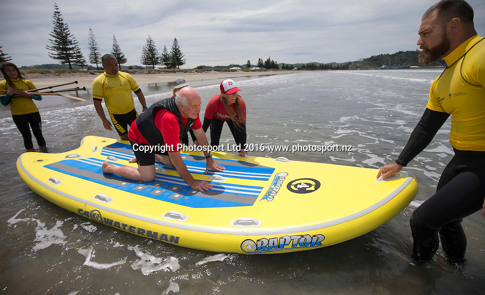 Pete Roberts has a go at surfing with Emma Lehtinen and Jane Alice from Hibiscus Surf school. Flight Centre Foundation Halberg Water Sports Day, Waikanae Beach, Gisborne, New Zealand. Saturday, 26 November, 2016. Copyright photo: John Cowpland / www.photosport.nz