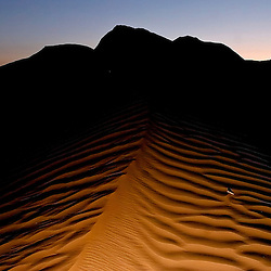052807     Brian Leddy.Rippling sand dunes at dusk give an other-worldly impression near Red Rock State Park on Monday. The photographer's flash illuminated the sand dunes to give them their rippling effect..