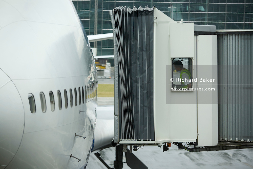 British Airways jetty operator carefully manoeuvres towards arrived BA aircraft door at Heathrow's Terminal 5.  .