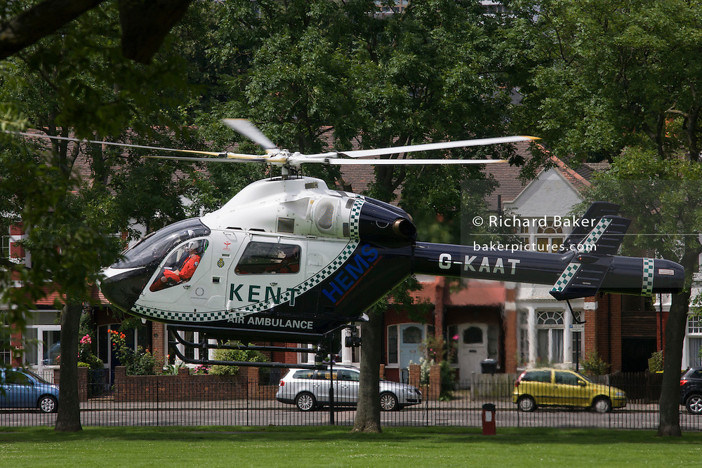 London 10/7/12. G-KAAT, a McDonnell Douglas MD-902 EXPLORER helicopter of the Kent Air Ambulance takes off past residential homes in a south London Park. The aircraft has just delivered a casualty to Kings College Hospital on Denmark Hill, Camberwell. Kent, Surrey & Sussex Air Ambulance Trust is a registered charity established to relieve sick and injured people in South East England and surrounding areas by providing a Helicopter Emergency Medical Service (HEMS).