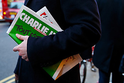 © Licensed to London News Pictures. 16/01/2015. LONDON, UK. A man carrying a copy of Charlie Hebdo's survival edition after buying it from 'La Page' book shop in London on Friday, 16 January 2015. Photo credit : Tolga Akmen/LNP