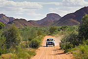 Four-wheel-drive vehicle on the Mereenie-Watarrka Road,  Gosse Bluff, Red Centre, Australia