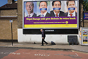 A voter walks underneath an anti-EU membership 'UK Independence Party's (UKIP) political billboard shows leader Nigel Farage and a gagged Prime Minister David Cameron, Labour party leader Ed Milliband and (coaltion) Deputy PM Nick Clegg - all silent against a bullying European Union, seen in East Dulwich - a relatively affluent district of south London. The ad is displayed before European elections on 22nd May.