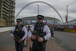 Armed police officers patrol outside Wembley Stadium following the FA Cup Final between Arsenal and Chelsea, as Britons have been encouraged to enjoy their Bank Holiday weekend as planned after police reviewed security at more than 1,300 events following the Manchester terror attack.