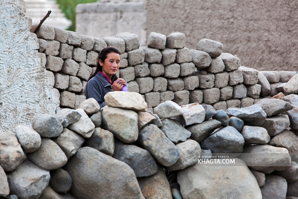 A ladakhi girl standing behind a stone wall built during the 2010 floods in Leh region of Ladakh