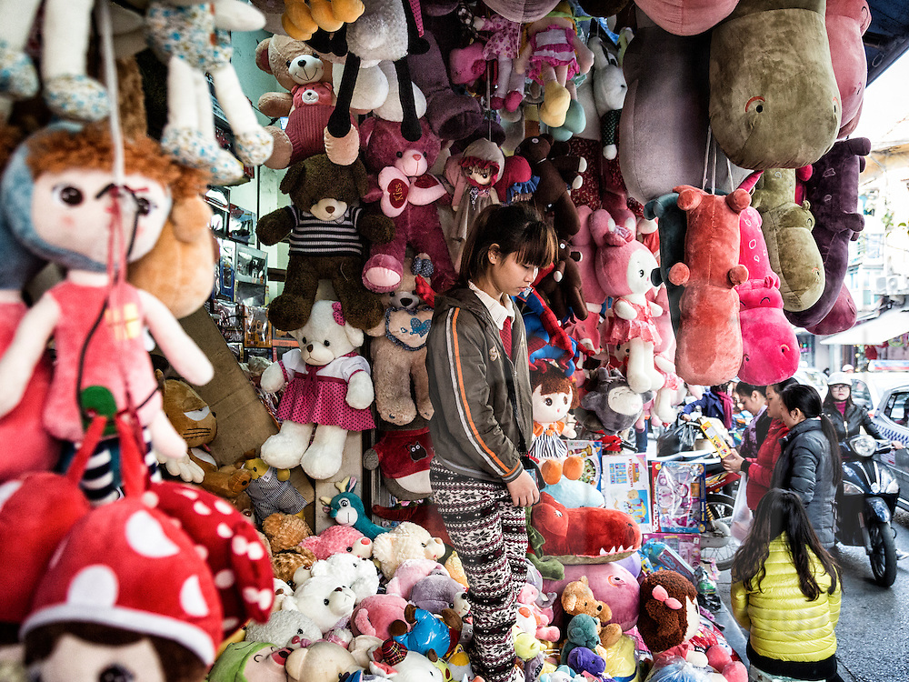 A girl is surrounded by stuffed animal toys in a small shop along Luong Van Can 'toy street' in Hanoi's Old Quarter, Vietnam, Southeast Asia