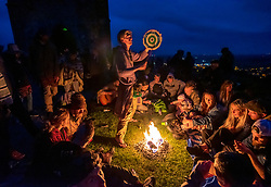 © Licensed to London News Pictures; 20/06/2020; Glastonbury, Somerset, UK. People gather round a fire as people gather on Glastonbury Tor for sunset on the Summer Solstice weekend on the longest day of the year today at midsummer. This year due to the coronavirus Covid-19 pandemic and concerns over social distancing at gatherings of people, Stonehenge and Avebury where thousands of people usually gather to celebrate the summer solstice are closed to the public, with the solstice live streamed from Stonehenge. Glastonbury authorities had also asked people to refrain from coming to Glastonbury for the solstice but hundreds came with many staying the night on the Tor. Glastonbury Tor is a hill outside Glastonbury town, topped by the roofless St Michael's Tower, a Grade I listed building which is what remains of the Church of St Michael built in the 14th century. The entire site is managed by the National Trust and has been designated a scheduled monument. Photo credit: Simon Chapman/LNP.