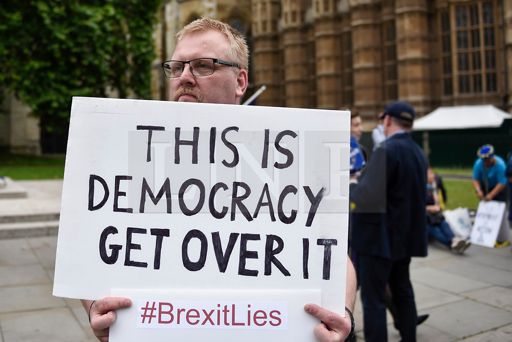 © Licensed to London News Pictures. 12/06/2018. LONDON, UK.  An anti-Brexit protester demonstrates outside the Houses of Parliament as MPs begin two days of debate and vote on amendments to the EU Withdrawal Bill.  Photo credit: Stephen Chung/LNP