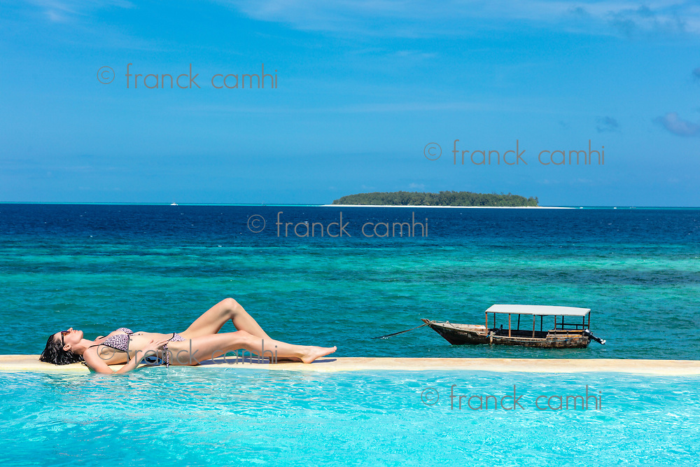 one caucasian woman enjoying vacations  sunbathing on a infinity swimming pool by the seaside looking at the idian ocean Muyuni  in Unguja aka Zanzibar Island Tanzania East Africa