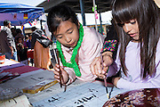 5th grader Annie Zeng, left, and 2nd grader Nicole practice writing Chinese characters during the Pomeroy Multicultural Festival at Pomeroy Elementary School in Milpitas, California, on April 25, 2015. (Stan Olszewski/SOSKIphoto)