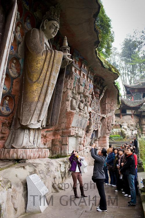 Tourists at Dazu rock carvings of Buddha of Mercy at Mount Baoding, Chongqing, China