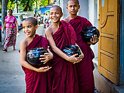 18 NOVEMBER 2017 - YANGON, MYANMAR: Buddhist novice monks wait for a donation in front of a business in Yangon. Pope Francis is visiting Myanmar, September 27-30. It will be the first visit by a Pope to the overwhelmingly Buddhist nation. He will meet with the Aung San Suu Kyi and other political leaders and will participate in two masses in Yangon. The Pope is expected to talk about Rohingya issue while he is in Myanmar. The Rohingya are persecuted Muslim minority in Rakhine state in western Myanmar. It's not clear how Myanmar's politically powerful nationalist monks will react if the Pope openly talks about the Rohingya. In the past, the monks have led marches and demonstrations against foreign diplomatic missions when foreign ambassadors have spoken in defense of the Rohingya. There is not much visible sign of the Pope's imminent visit in Yangon, which is estimated to be more than 90% Buddhist.    PHOTO BY JACK KURTZ