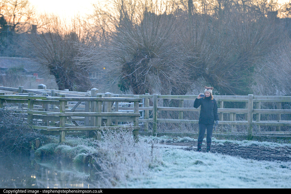 © Licensed to London News Pictures. 29/12/2013. East Bergholt, UK. A woman stops to take a photograph at Flatford Mill. Early morning frost and mist on the River Stour at Deadham Vale this morning 29th December 2013. Photo credit : Stephen Simpson/LNP
