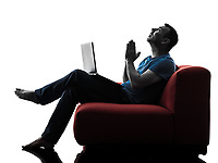 one caucasian man sofa couch computer computing laptop praying in silhouette isolated on white background
