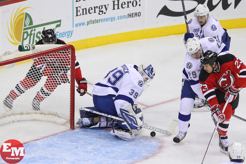 Feb 7, 2013; Newark, NJ, USA; Tampa Bay Lightning goalie Anders Lindback (39) makes a save on New Jersey Devils center Adam Henrique (14) while Tampa Bay Lightning defenseman Brendan Mikkelson (29) and New Jersey Devils center David Clarkson (23) during the first period at the Prudential Center.