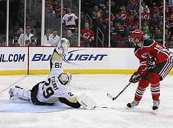 Mar 17, 2010; Newark, NJ, USA; Pittsburgh Penguins goalie Marc-Andre Fleury (29) makes a glove save on New Jersey Devils center Travis Zajac (19) during the second period at the Prudential Center.