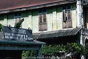 The Gerai Makanin/Dan Minuman Muslim restaurant stands below a building exhibiting the architectural influence of British colonialism in Penang Malaysia's Georgetown district.